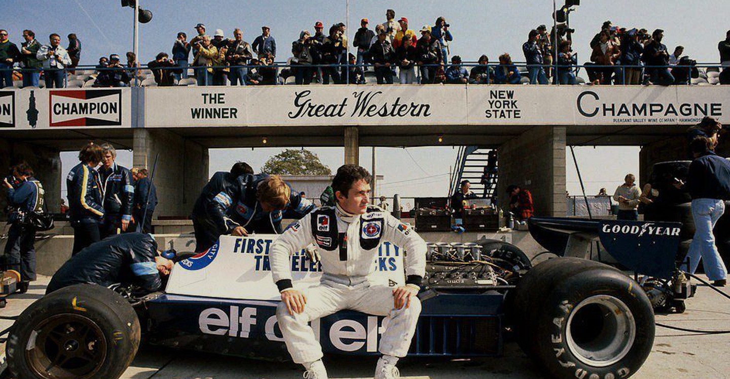 A race car driver sitting on his car with the Great Western logo in the background
